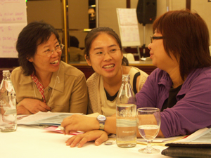 May Wong of AMRC confers with Chinese colleagues Liu Xiufang of the Occupational Health Resources Centre and So Sheung of the Labour Education and Service Network.